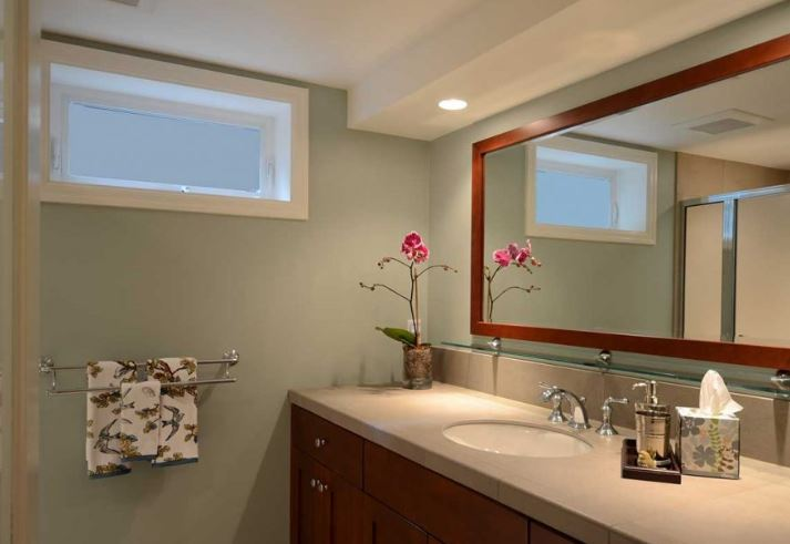 bathroom remodel in basement with small window and large countertop with single sink and small stand up shower 1