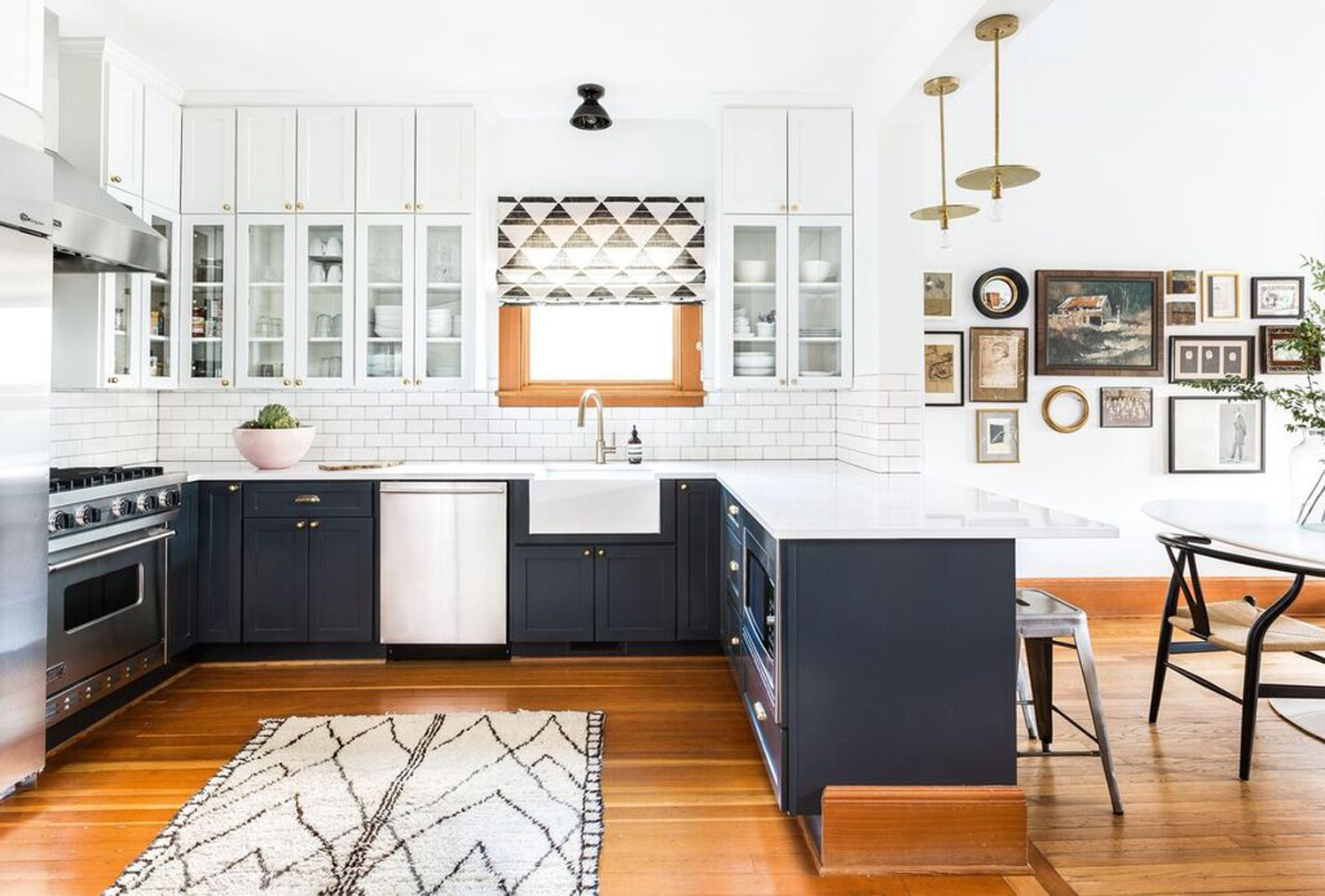 beautiful modern and light kitchen with white countertops and dark navy blue cabinets with wood flooring