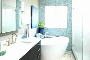 bright bathroom with extended vanity and extra countertop space, blue tile across wall and modern tub with stand up shower and glass shower doors
