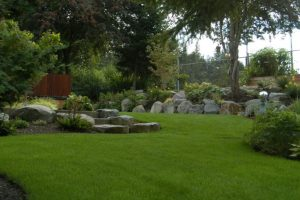 clean landscaping with green grass, flower beds, trees, and custom rock path and retaining wall
