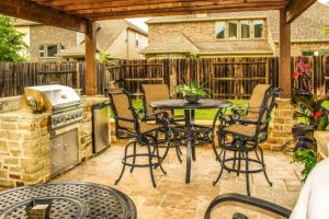 custom grill and outdoor kitchen with grill stone walls and tile outside pavers with dining room set