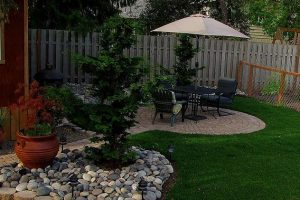 custom landscaping with large river rock, custom patio with sitting area, separate garden, and custom plants and trees