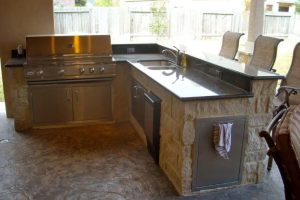 custom outdoor kitchen with large grill, dishwasher, running water, and bar stool seating under covered porch