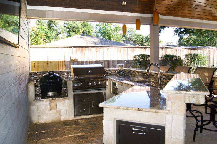 custom outside kitchen with lots of counterspace large grill sink running water and lighting