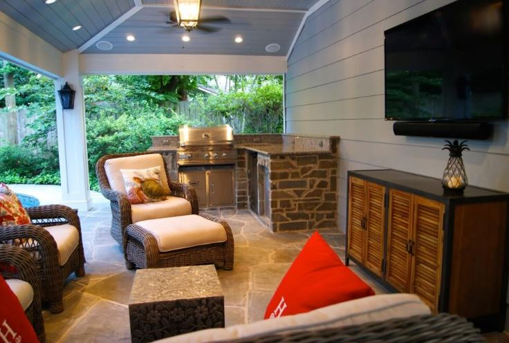 custom stone kitchen with seating around tv under covered porch and ceiling fan and stone flooring