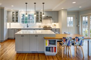 kitchen remodel in Spokane that features an open concept with white countertops, a large kitchen island, pendant lighting, and new light gray cabinets.