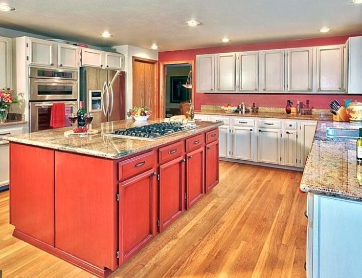 large kitchen island with red cabinets underneath white cabinets surround the wall stove top on the center island and new wood flooring