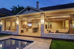 large outdoor kitchen under covered patio with full kitchen and living space to watch tv and entertain