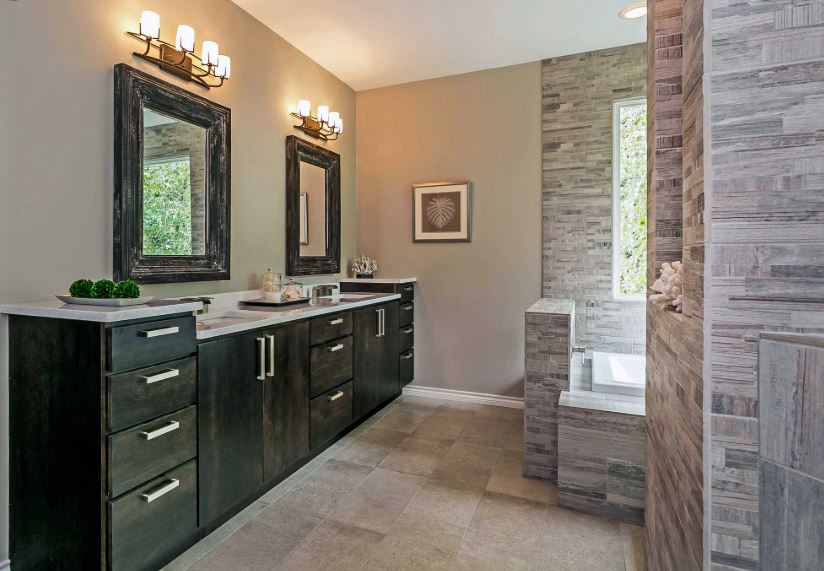 master bathroom with double sink and raised countertop next to vanity, built in tub, and walkin shower