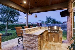 outdoor kitchen counter top with built in large grill and bench sitting with tv and lighting all under covered porch