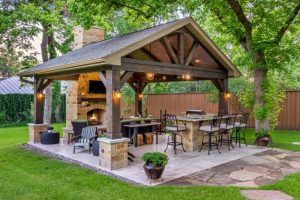 outdoor kitchen under a spearate gazebo covered porche with fireplace and dining area