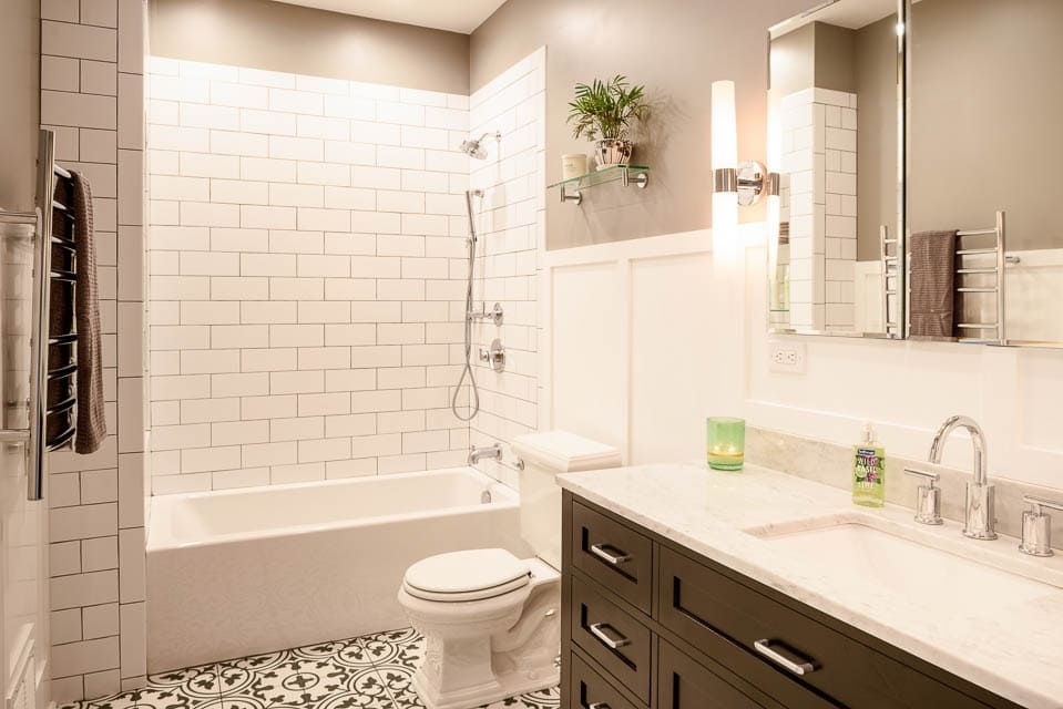 subway tile shower surround with elegant looking custom tiles floors and large counter top wth one sink