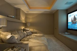 theater room in basement with brown walls a projector and theater screen 1