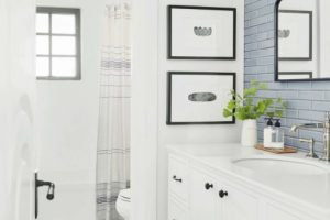very white bathroom with white cabinets, tile work, and black fixtures with blue subway tile backsplash