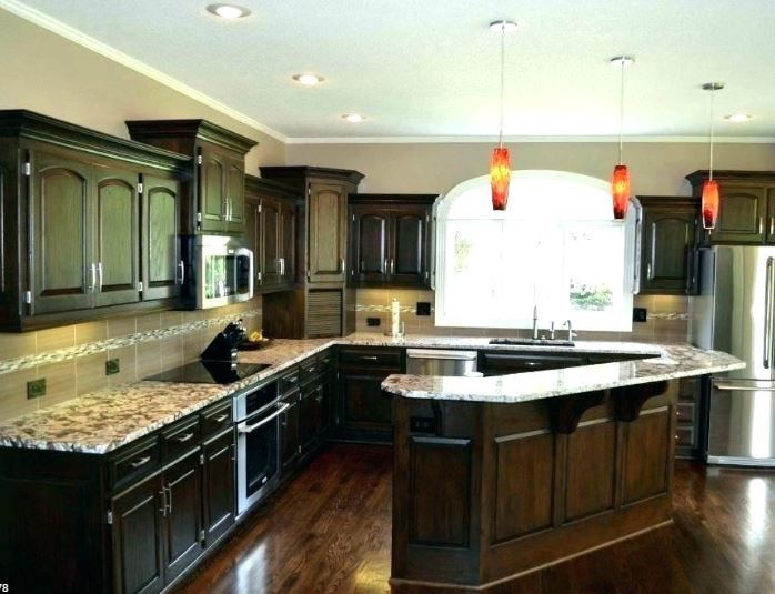 walnut cabinets with wrap around countertops and pendant lights large window and recessed lighting