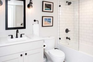 white and clean bathroom remodel with black fixtures and subway tile shower surround and glass shower door