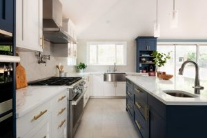white kitchen remodel with two-toned colored cabinets and brand new white quartz countertop and gold cabinet handles and knobs